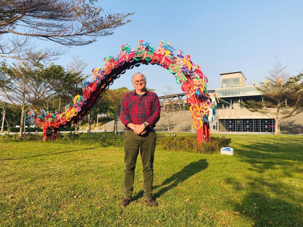 David Gerstein standing in front of his peloton piece in Taiwan